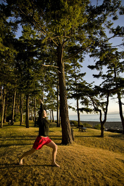 A woman in yoga pose by the ocean at Kitty Coleman Beach campground in the Comox Valley.