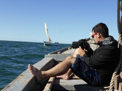 Un homme sur une barque, assis, un appareil photo dans la main. Une autre barque arrive sur la droite de l'image.