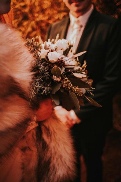Ein Bräutigam und eine Braut mit Brautstrauß.