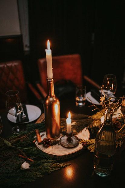 Eine Kerze leutet neben einer Flasche.