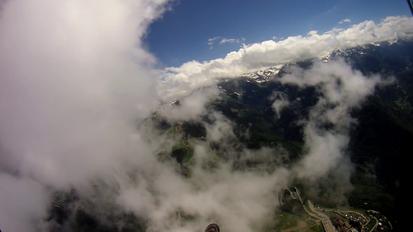 Superbe vue d'un parapente qui traverse un nuage.