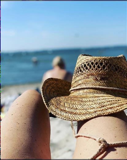 Sue Blonds Knie am Strand mit einem Strohhut