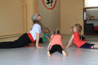 eine Frau macht mit mehreren Kindern eine Yogaposition auf dem Boden in einem Yogastudio