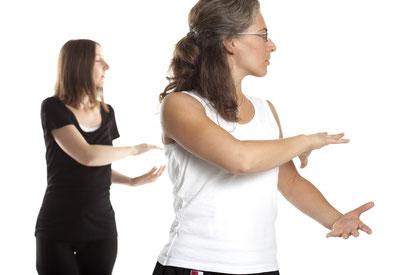 zwei Frauen machen Tai Chi, sie haben sich nach links eingedreht und halten die Hände als würden sie einen Ball tragen