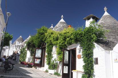 Eine Gasse mit eingeschossigen runden, weißen Steinhäusern mit grauen, spitzen Dächern. Die Häuser sind bewachsen, der Himmel im Hintergrund strahlend blau