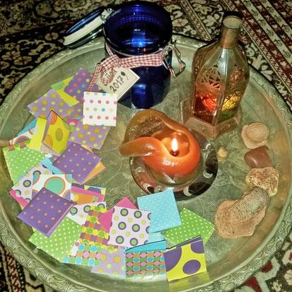 Marokkanischer Teetisch mit Kerze, dem blauen Glas und bunten, zusammengefalteten Zettelchen