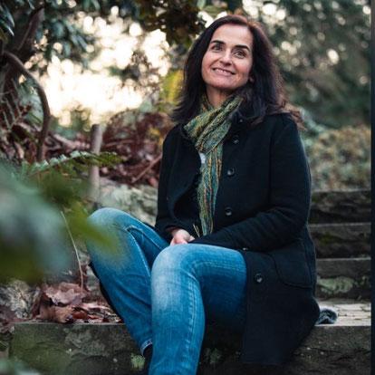 Iris Felder Glücks-Coach. lachende dunkelhaarige Frau sitzt auf Treppe in der Natur