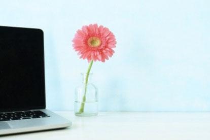オフィスのテーブルに飾られたガラスの花びん。パステルカラーのバラの花たち。