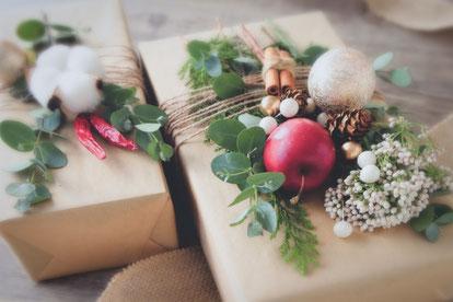 積まれた書籍のうえに置かれたコーヒーのマグカップ。花びんに活けられた黄色の菜の花。