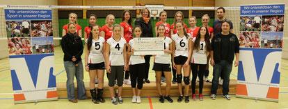 Strahlend nahmen die U18-Volleyballerinnen unter der Leitung von Trainer Maik Kutzer den Scheck von Claudia Schünemann entgegen.