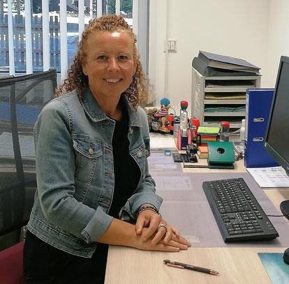 Die Schulsekretärin Sabine Boscher lachend an ihrem Schreibtisch.
