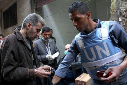 Lors d'une distribution de nourriture par l'UNRWA, l'agence de l'ONU chargée des réfugiés palestiniens au Proche-Orient, dans le camp de réfugiés de Yarmouk (Syrie), en mars 2015. HANDOUT/REUTERS