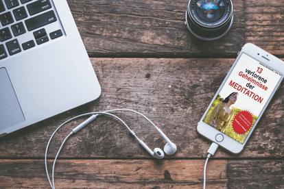 Foto von einem Handy mit dem Ebook Cover 13 verlorene Geheimnasse der Meditation +  Kopfhörer