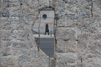 A pedestrian can be seen through a hole in the rest of the Berlin Wall