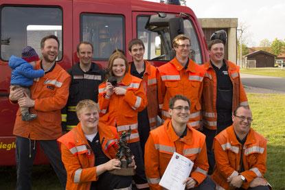Mitglieder der Freiwilligen Feuerwehr in Hüde haben sich in Uniform vor einem Feuerwehrfahrzeug zu einem Gruppenfoto aufgestellt.