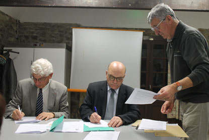 M Adrien Le Formal, assis à gauche sur la photo et F Jean-René Gentric, assis à droite sur la photo, signent les documents sous le regard attentif de Jean-Jacques Le Floch, président de l'Associaton