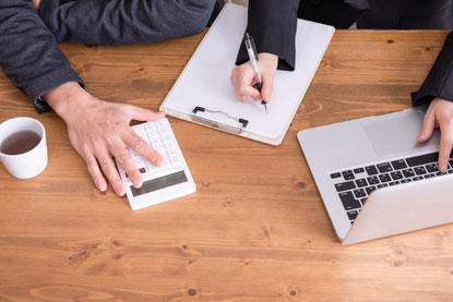 広げられたノートとピンクの電卓とボールペン、眼鏡。