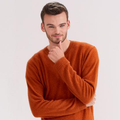 Mann lächelt in einem kuscheligen Pullover in die Kamera