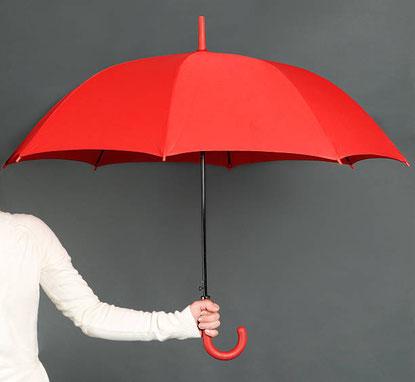 Zur Hälfte sichtbare Person in weiß hält roten geöffneten Regenschirm vor eine graue Wand.