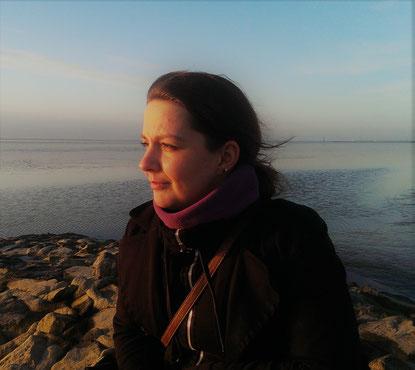 Auf dem Bild ist die Autorin zu sehen. Die steht auf Steinen, die am Meer liegen und guckt zur Seite. Ihr Gesicht wird dabei von der Sonne beschienen.