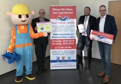 Organisationsleiter Werner Berning und Bürgermeister Manfred Wellen präsentieren das Messeplakat vor dem Rathaus in Lohne.