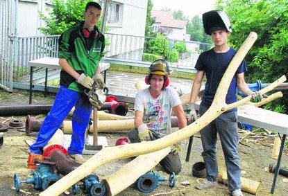 Thomas Putze, ein Bildhauer und Künstler aus Stuttgart (Mitte), fertigt mit Schülern der Bickeberg-Schule eine Skulptur aus Holz und Schrott-Material.  Bild: Spille