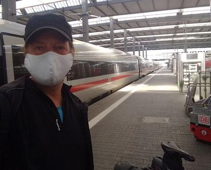 ein Mann mit Maske vor einem ICE im Münchener Hauptbahnhof