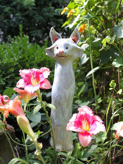 Katze aus Keramik in grau im Garten mit Taglilien