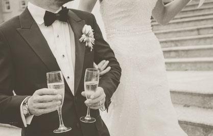 Detailaufnahme eines Brautpaares mit Sektkelchen in der Hand.