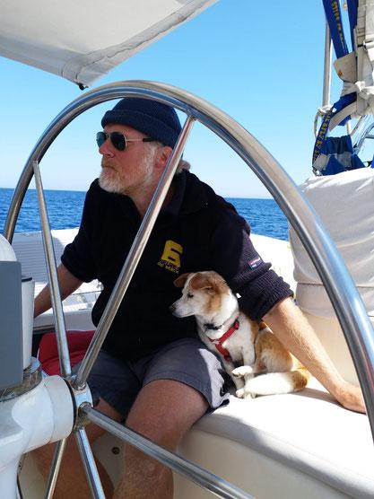 Mann sitzt am Steuerrad auf einem Segelboot