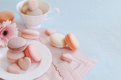 お皿とティーカップに盛られたピンクのマカロン。ピンクのデイジーの花。