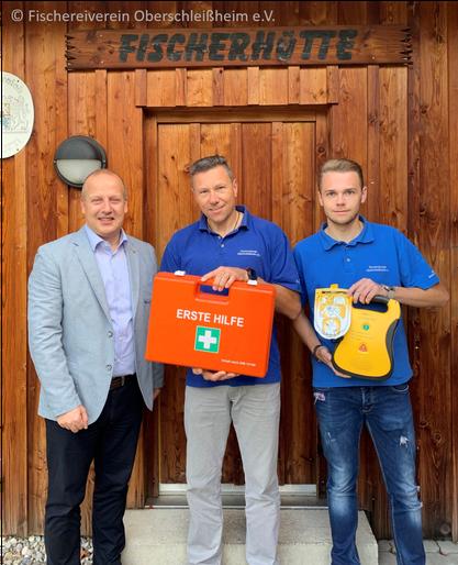 rechts: Projektleiter Simon Langhammer (Fischereiverein) mit Defibrillator; Mitte: 1. Vorstand Ralph Langhammer (Fischereiverein) mit ErsteHilfe-Koffer; links: Filialdirektor Ronny Sonnekalb (Münchner Bank eG);