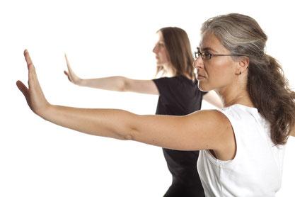 Zwei Frauen machen sanfte Bewegungen, sie strecken beide einen Arm von sich