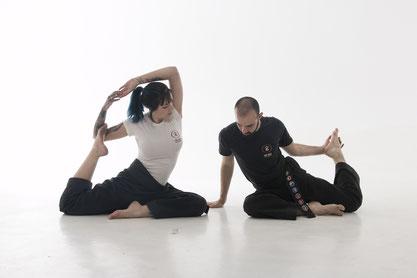 Ein Mann und eine Frau sitzen auf dem Boden und machen Yogapositionen, sie dehnen sich