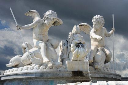 Eine Gruppe von weißen Skulpturen, bestehend aus zwei kleinen Engeln, die mit Werkzeugen und Wasser spielen.