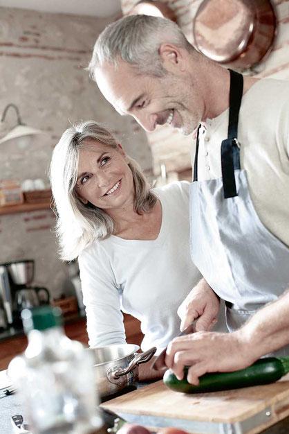 Pärchen mittleren Alters beim gemeinsamen Kochen in Küche