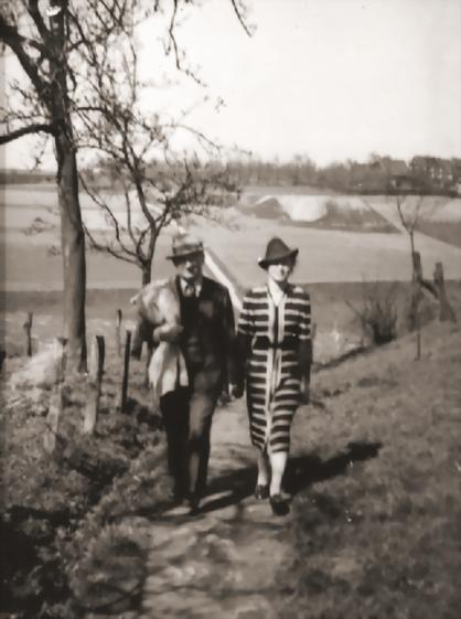 """Historisches Foto: Hanns und Erna Heinen kurz nach dem Erwerb des """"Schwarzen Hauses"""" im Jahre 1932. Im Hintergrund – auf der anderen Talseite - die Abraumhalde der Bleimine und das """"Schwarze Haus"""""""
