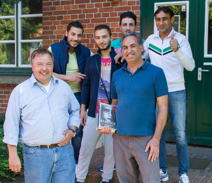 Lorenz Hartwig (links) mit Flüchtlingen vor der Alten Schule während des Aufbaus des Bücherbasars. Sie packten tatkräftig mit an.