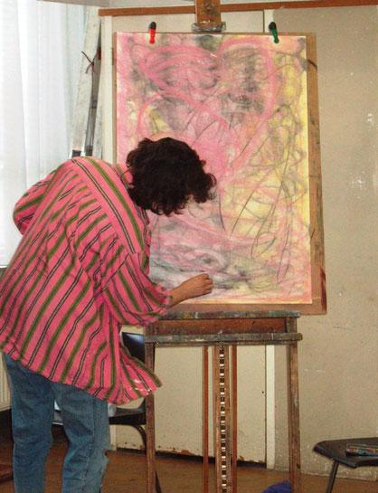 Een vrouw met donkerhaar staat voor een ezel met een groot vel papier. Ze tekent met krijt, grijs, zacht geel en roze  en is volop in beweging om haar intuïtieve gebaren op papier te brengen.
