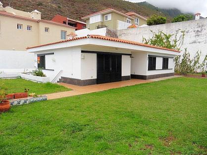 Ebenerdiger Bungalow mit viel Rasenfläche um das Haus.