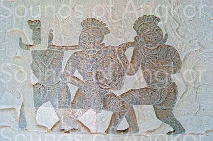 Gong à mamelon sur portant percuté avec une mailloche. Angkor Vat, 3e galerie nord. Victoire de Krishna sur l'Asura Bāna. XVIe s.