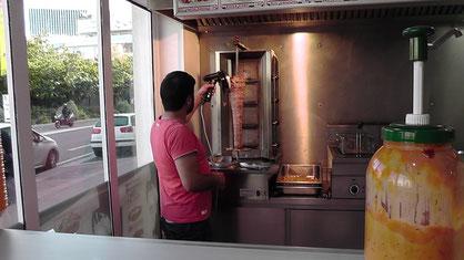 Imbiss-Inhaber macht mir einen Döner mit Pommes Frites