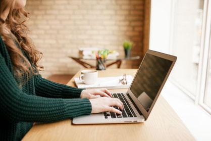 Junge Frau arbeitet am Laptop in modernem Büro