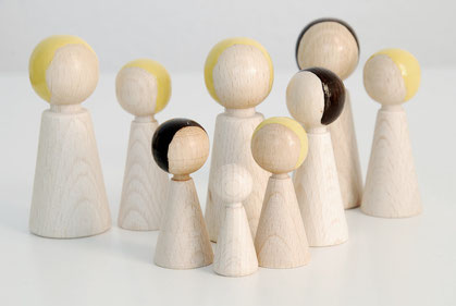 Holzpüppchen in verschiedenen Größen und anderen unterschiedlichen Merkmalen stehen als Familienaufstellung beieinander