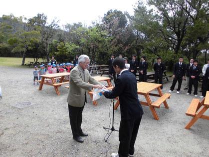 指定管理者・沖縄美ら島財団の常務理事・花城より記念品を贈呈しました
