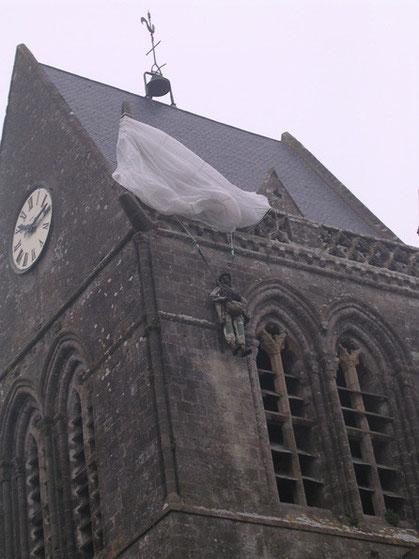 Touristische Attraktion oder ewige Mahnung nicht zu Vergessen? Die Fallschirmjägerpuppe am Kirchturm erinnern an den jungen Soldaten der am 6. Juni für 24 Stunden tod dort oben hing.