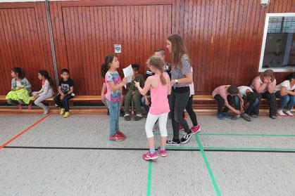 Schülerinnen und Schüler der Klasse 4e beraten sich mit ihrer Klassenlehrerin