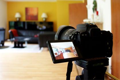 Immobilienfoto; Kamera, die gerade ein Wohnzimmer aufnimmt.