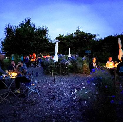 Im Garten sitzen mehrere Personen an kleinen Tischen, die von Laternen beleuchtet werden.