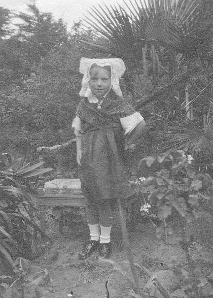 Jeanne enfant portant le costume traditionnel de l'île pour une fête la coiffe, le châle croisé et la jupe noire